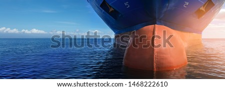 Close up of large blue merchant crago ship in the middle of the ocean underway. Performing cargo export and import operations with sun rays, horizon line and beautiful sky.