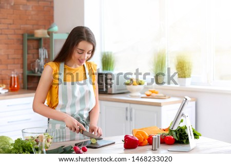 Beautiful woman preparing tasty vegetable salad in kitchen at home #1468233020