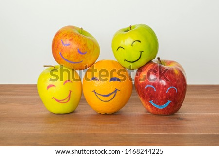 Different apples and orange with funny faces, tolerance, originality or friendship concept.  Royalty-Free Stock Photo #1468244225