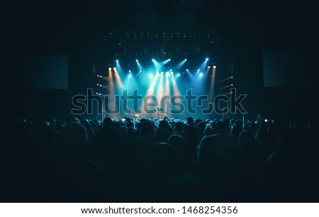 Concert crowd in club.Bright stage in big nightclub full of young people on dance floor.EDM musical festival audience waiting for the show to begin.Youth entertainment event in crowded music hall #1468254356