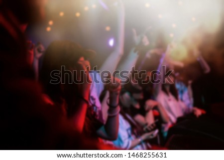 Blurred background with group of happy music fans dancing to favorite dj performing on stage in night club.Young people partying to the rap singer performance in bright lights #1468255631
