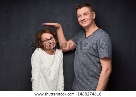 Studio waist-up shot of tall man smiling and showing with hand at height of short girl standing beside him and looking with perplexity at camera, over gray background. Variety of person's heights #1468274618