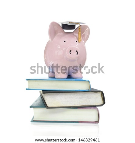 piggy bank with graduation cap on a pile of books                                #146829461