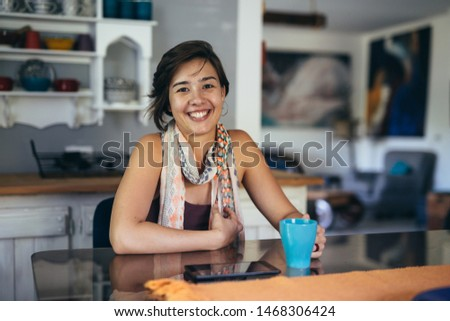 woman drinking coffee and using tablet at her home #1468306424