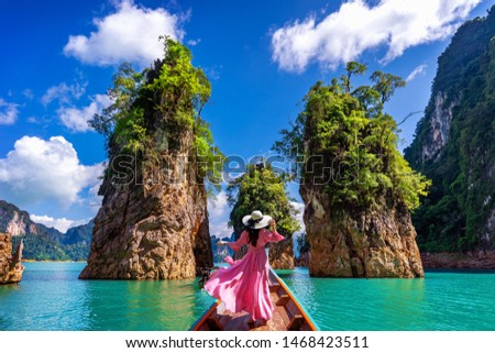 Beautiful girl standing on the boat and looking to mountains in Ratchaprapha Dam at Khao Sok National Park, Surat Thani Province, Thailand. #1468423511
