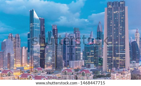 Skyline view of the buildings of Sheikh Zayed Road and DIFC night to day transition timelapse in Dubai, UAE. Illuminated skyscrapers in financial centre aerial view from above in downtown #1468447715