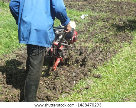 Farmer plowing the land in the garden with a hand tractor cultivator,Soil cultivation.  #1468470293