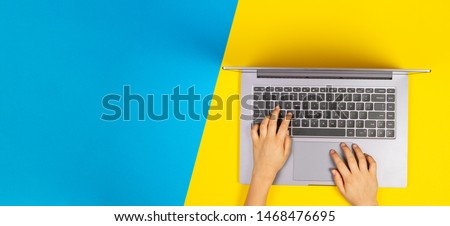 Kid hands typing on laptop computer keyboard, top view, yellow and blue background #1468476695