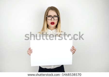 young beautiful business woman in eyeglasses holding blank sheet of paper isolated white background space for text #1468538570