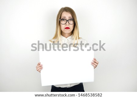 young beautiful business woman in eyeglasses holding blank sheet of paper for announcement isolated white background space for text #1468538582