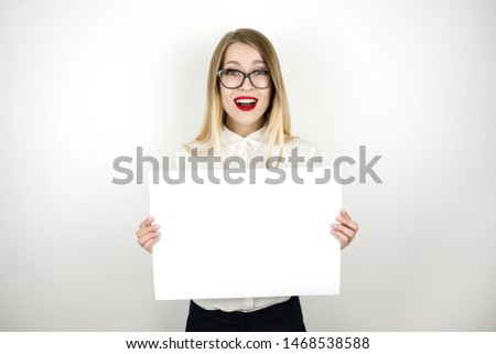 young happy business woman in eyeglasses holding blank sheet of paper for announcement isolated white background space for text #1468538588
