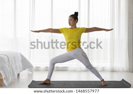 Middle-aged Asian woman wearing sportswear practice yoga on the mat. (Warrior Pose) Standing on both arms One leg bent over the knee to the front The other leg stand straight. Bedroom background #1468557977