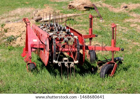 Dilapidated agricultural farming hay tedder turning equipment left in local field after heavy usage surrounded with green grass on warm sunny spring day #1468680641