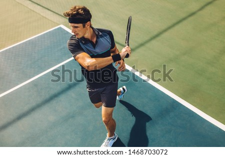 Focused young male tennis player hitting a forehand. Tennis player playing a match on hard court. Royalty-Free Stock Photo #1468703072
