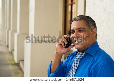 Handsome middle age Hispanic man in an urban setting with a wireless phone. #146871524