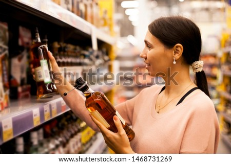 A beautiful girl takes alcoholic drinks from the supermarket shelf. Shopping for alcohol in the store.  #1468731269