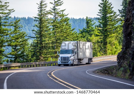 Big rig white powerful American bonnet long haul semi truck transporting commercial cargo in refrigerated semi trailer moving uphill on winding road with a green trees and safety fence on the side #1468770464