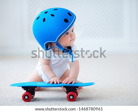 cute infant baby girl in protective helmet outfit ready to ride skateboard, extreme sport concept #1468780961