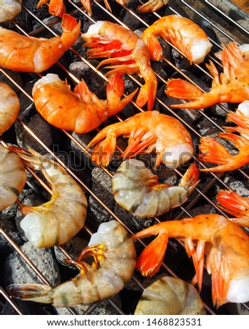Grilled shrimp BBQ on Charcoal prawns Colorful seafood picture Outdoor food summer camping Simple cooking barbeque grill top view with charcoal Shellfish Food allergy Keto diet option