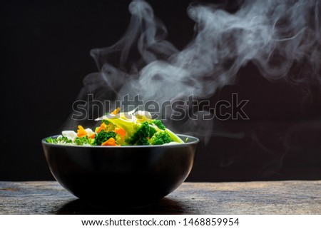 The steam from the vegetables carrot broccoli Cauliflower in a black bowl, a steaming. Boiled hot Healthy food on table on black background,hot food and healthy meal concept #1468859954