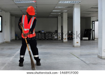 Janitor is sweeping dust on the office floor. #1468919300