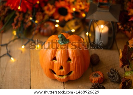 Halloween pumpkin with leaves on an old wooden table with luminous lights and an old lamp. Autumn mood and atmospheric photo #1468926629