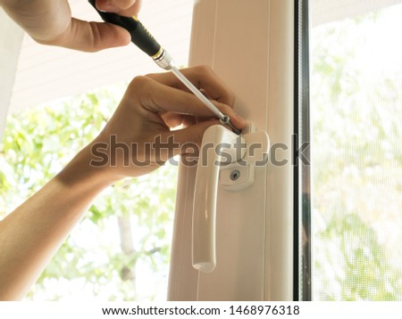 a man fixes a window, fastens a handle close up #1468976318