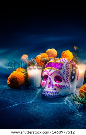 """Traditional sugar skull used at mexican offerings or """"ofrendas"""" for Day of the Dead celebration with marigold or """"cempasuchil"""" flowers. high contrast image #1468977512"""