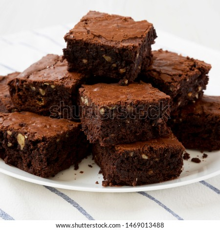 Homemade chocolate brownies on a white plate, side view. Closeup. #1469013488