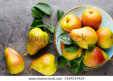 Fresh bio pear with leaves on the plate. Gray stone table. #1469014424