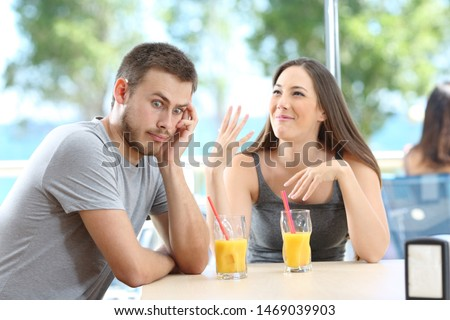 Bored man listening her friend talking in a bar or hotel on the beach #1469039903