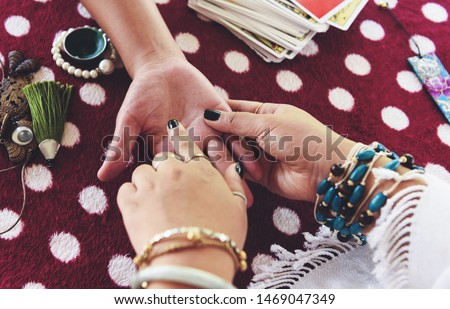Fortune teller reading fortune lines on hand Palmistry Psychic readings and clairvoyance hands concept with Tarot cards divination / Palm reading #1469047349
