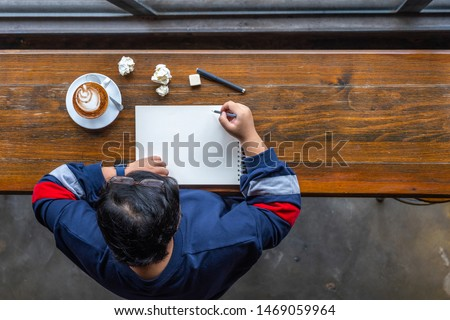 Top view of Asian freelancer drawing on sketchbook at coffeeshop #1469059964