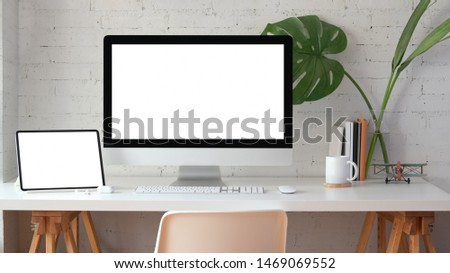 Stylish home office with blank screen desktop computer and tablet with stationery #1469069552