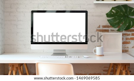 Blank screen desktop computer in minimal office room with decorations and copy space