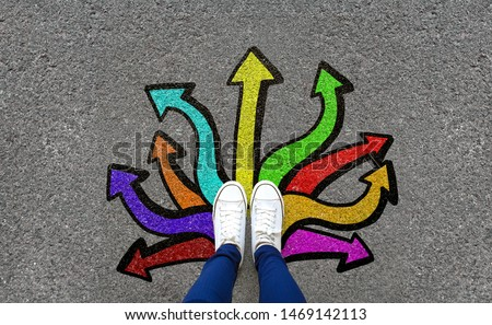 Feet and arrows on road background. Pair of foot standing on tarmac road with colorful graffiti arrow sign choices, creative and idea concept. Selfie woman wearing white shoe or sneaker. Top view. #1469142113