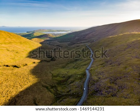 Aerial view of Conor Pass, one of the highest Irish mountain passes served by an asphalted road, located on the south-western end of the Dingle Peninsula, County Kerry, Ireland #1469144231