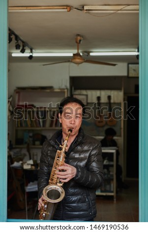 Shanghai, China - March 23, 2019.  Asian man plays saxophone in the window of his music training studio. #1469190536