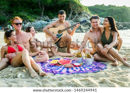 Group of happy friends on a tropical island having fun - Young adults playing together on the beach, summer vacation on a beautiful beach
