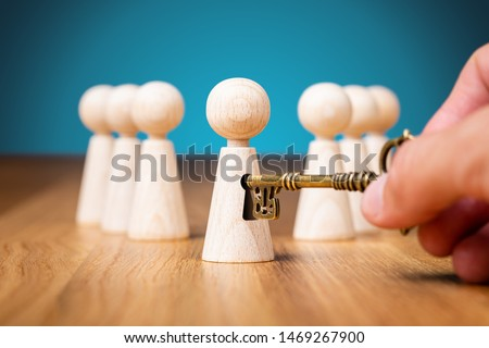 Coach unlock potential - motivation concept. Coach (manager, mentor, HR specialist) unlock leader potential and talent represented by wooden figurine and hand with key. Royalty-Free Stock Photo #1469267900