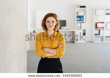 Happy relaxed confident young businesswoman standing with folded arms in a spacious office looking at the camera with a warm friendly smile Royalty-Free Stock Photo #1469286803