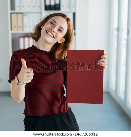 Cheerful successful young job applicant giving a thumbs up with a beaming smile while holding up her CV to show that she has been appointed to the post. Bewerbung is german word for application file #1469286812