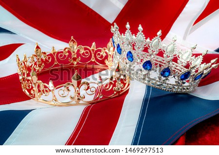 British royals, royal coronation and monarchy concept theme with a gold king crown and a silver queen tiara with the UK flag called the union jack in the background #1469297513