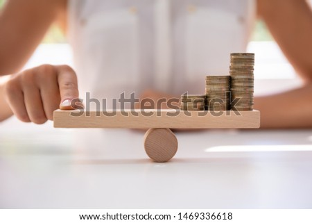 Close-up Of A Businessperson Balancing Increasing Stacked Coins With Finger On Seesaw #1469336618