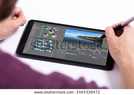 Young male editor editing video on tablet at workplace