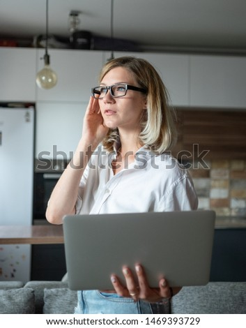 Young woman working with a laptop at home with mobile phone #1469393729
