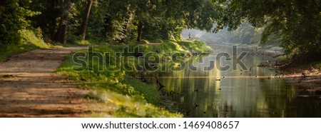 Tree Lined Serene Walking and Jogging Path in the Morning with Dappled Sun Light and a Calm River at Great Falls Park in Maryland USA Royalty-Free Stock Photo #1469408657