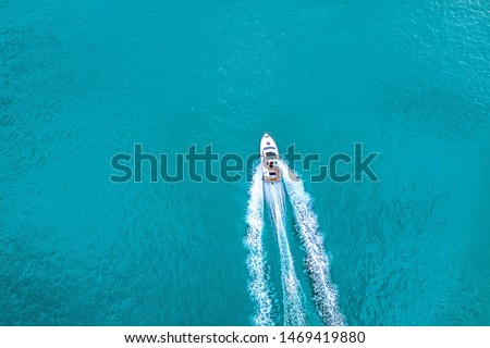 Speed boat on  azure sea in turquoise blue water -  birdseye aerial view of boat Royalty-Free Stock Photo #1469419880