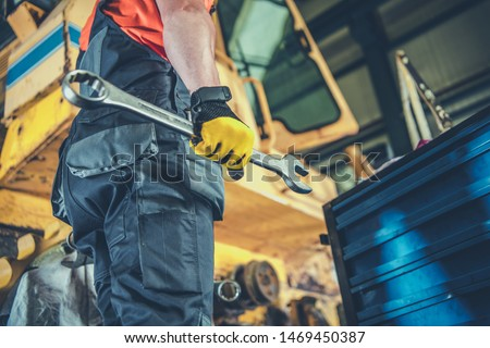 Caucasian Men with Large Iron Wrench Fixing Heavy Machinery. Industrial Job. Royalty-Free Stock Photo #1469450387