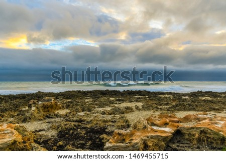 Limestone rock formations on a Florida beach with a cloudy morning sky and waves breaking and blowing in the wind. Royalty-Free Stock Photo #1469455715